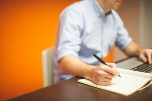 אדם יושב ליד שולחן עם דף ועט